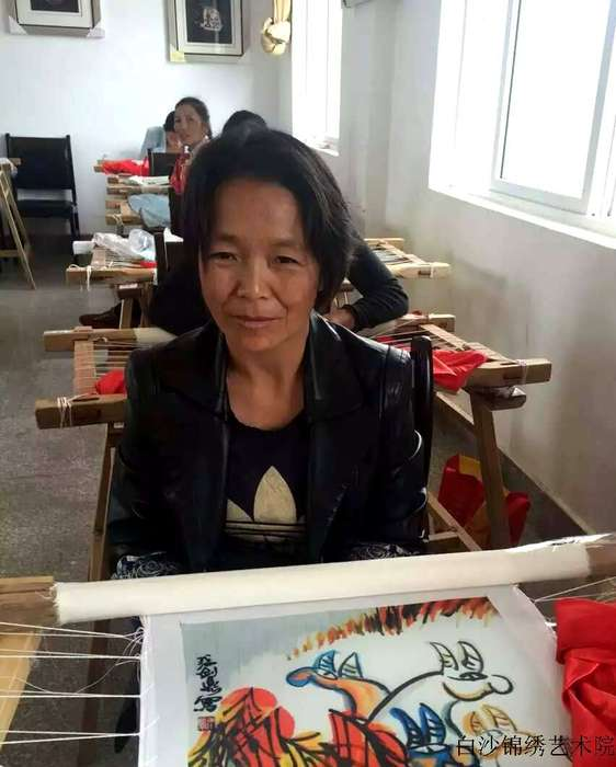 He Xiumei, who has leg problems is very excited and happy within been enrolled into the embroidery branch of Baisha Naxi Embroidery Institute
