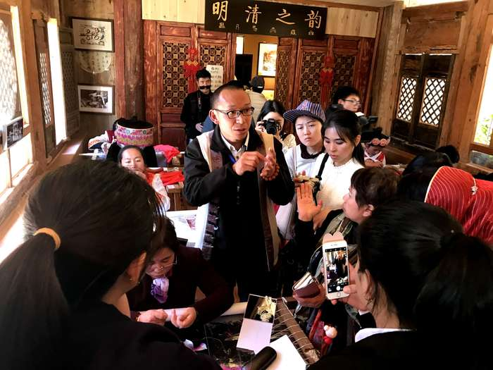 Weiyuancai the vice principal of Lijiang Naxi Embroidery Institute is introducing the eithnic culture and embroidery process to the diplomats from South Asian countried